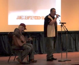 James Dempsey singing at a microphone with Darren Minifie sitting playing acoustic guitar.