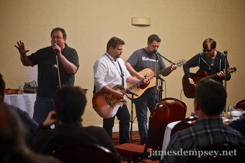 James Dempsey sings while Daniel Pasco, Ben Scheirman and Jonathan Penn play guitar for the Breakpoint Jam at CocoaConf Boston 2013