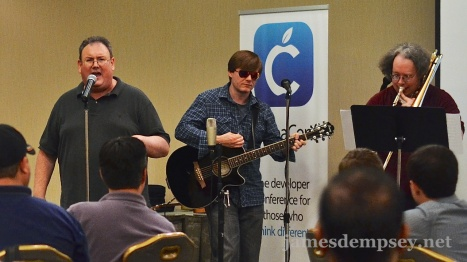 James Dempsey at the microphone, Jonathan Penn playing guitar and Mark Dalrymple playing trombone at CocoaConf DC.