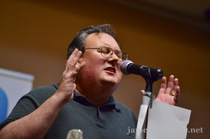 James Dempsey singing at a microphone