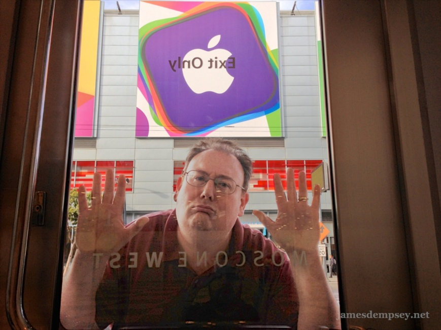 James Dempsey with hands and face pressed up against door to Moscone West, unable to get into WWDC.