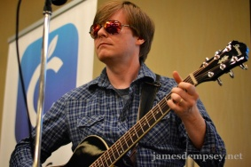 Jonathan Penn in mirrored sunglasses playing guitar