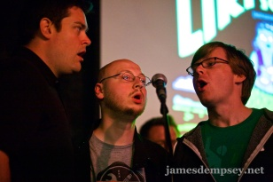 Nathan Eror, Uli Kusterer and Jonathan Penn gathered around a microphone singing The Liki Song