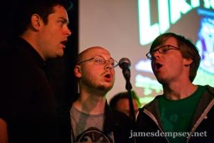 Nathan Eror, Uli Kusterer and Jonathan Penn gathered around a microphone singing The Liki Song