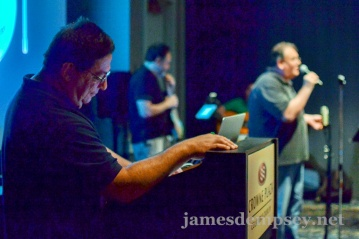 Daniel Steinberg at podium with James Dempsey, Eric Knapp and Will LaFrench playing in background.