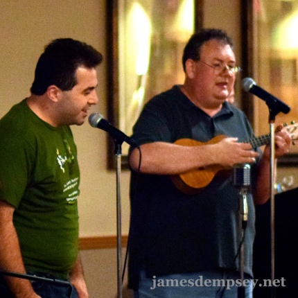 Matt Smollinger singing at microphone with James Dempsey playing ukulele